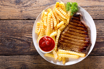 plate of grilled beef steak with french fries