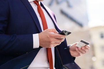 Businessman works with credit card and telephone.