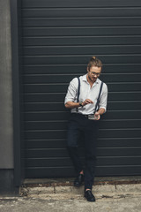 Stylish young businessman in spectacles holding ashtray while smoking