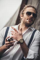 Portrait of bearded handsome man in sunglasses lighting cigarette with lighter
