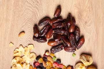 Mix of dried nuts and fruits on wooden background
