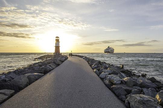 Schiff verläßt den Hafen von Warnemünde hinter einem Leuchtturm im Sonnenuntergang