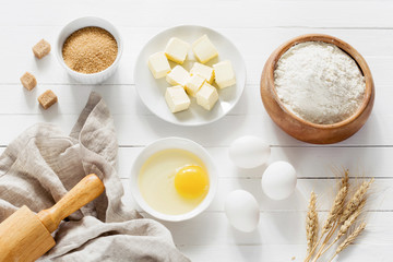Ingredients for baking pastry / cake / cookies on white wooden table. Top view