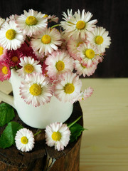 Bouquet of daisies in a white jug on a stump on a wooden background. Close-up photo