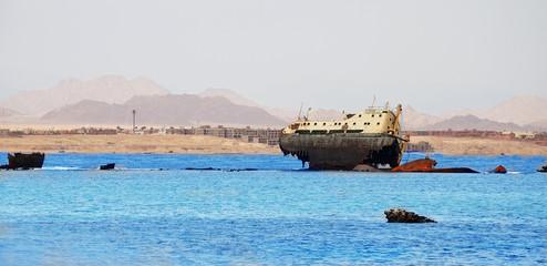 Old rusty sunken ship in water