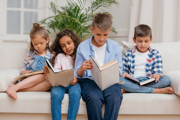 multicultural group of focused children reading books while sitting on sofa at home