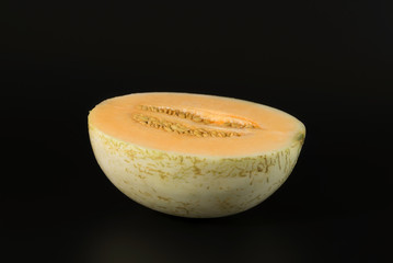 Cantaloupe melon half cut sliced isolated on black background.