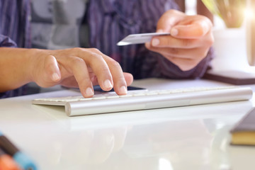 Online payment :  male hands holding a credit card and typing PC keyboard for online shopping.