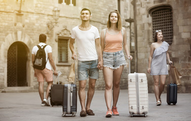 Active man and woman in shorts with luggage