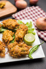 Crispy onion bhajis or kanda or pyaj ke pakore or pakoda , delicisous indian and brazilian street food on salad, typically enjoyed in rainy / monsoon season with hot tea, selective focus