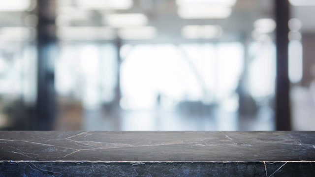Black stone table top and blurred bokeh office interior space background - can used for display or montage your products.