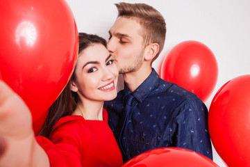 handsome guy kisses his pretty girlfriend on the cheek and making selfie on a white background
