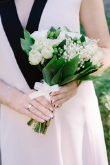 Charming lily of the valley wedding bouquet in hands of the bride