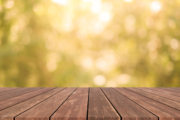 blur warm tone color of nature background with glow sunshine light and aged wood table top shelf perspective view for promote product concept.