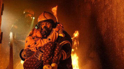 Brave Fireman Descends Stairs of a Burning Building and Holds Saved Girl in His Arms. Open fire and one Firefighter in the Background.
