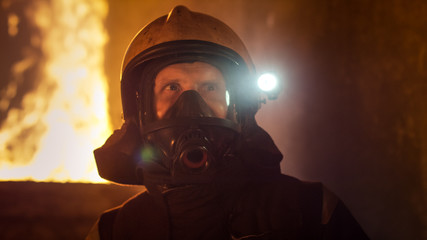 Portrait of a Brave Firefighter Standing in a Burning Building. Raging Fire in the Background.