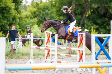 Young rider girl on bay horse training jumping over obstacle with her trainer