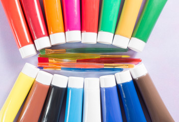 Multicolored acrylic paints tubes set with five colorful brushes