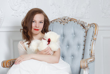 A dark-haired girl in a white dress sits in a deep armchair and holds a teddy bear