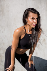 Beautiful young woman in black sexy leggings with pretty athlete muscular body listen music with headphones. Crossfit training urban area street gym city workout exercise routine healthy lifestyle.