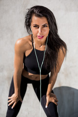 Beautiful strong woman in black sexy leggings with pretty athlete muscular body listen music with headphones. Crossfit training urban area street gym city workout exercise routine healthy lifestyle.