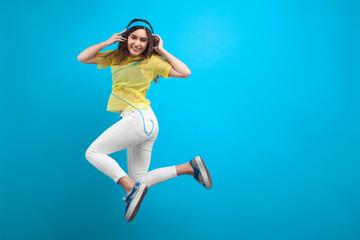 Smiling brunette girl in headphones jumping