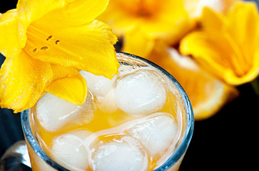 Cold orange juice with ice decorated with a Lily flower.