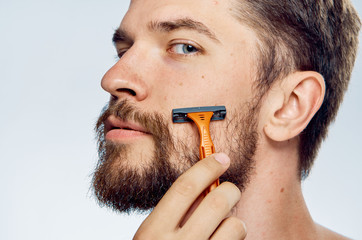 Young guy with a beard on a white isolated background shaves