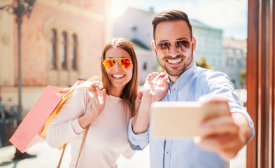 Beautiful young couple enjoying in shopping. Consumerism, fashion, lifestyle concept