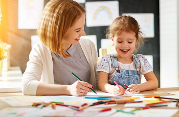 mother and child daughter draws in creativity in kindergarten