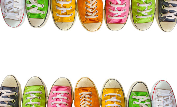 Variety of the colorful leather shoes on a white background.  sneaker shoes on , cool youth white yellow blue black gym shoes standing in circle on white background, Top view