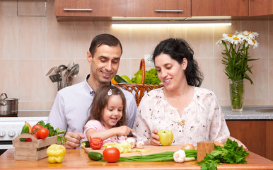 happy family with child in home kitchen interior with fresh fruits and vegetables, pregnant woman, healthy food concept
