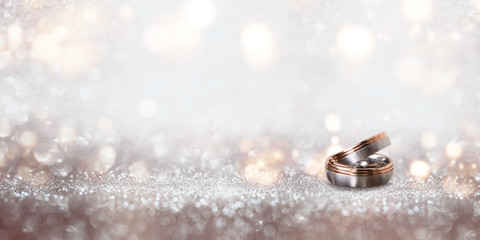 Wedding rings on an abstract silver glittering bokeh background