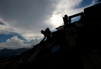 A woman is silhouetted as she carries bricks from the debris of a monastery damaged during the 2015 earthquake, in Swayambhunath Stupa, in Kathmandu