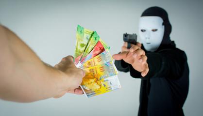 Mann mit einer Waffe bedroht jemanden und erhält Geld