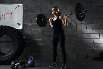 Young woman working out using barbell with heavy weights in a fitness club.