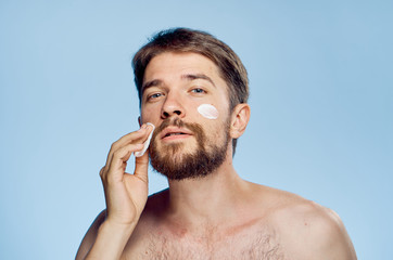 Young guy with a beard on a blue background, a cometic face cream