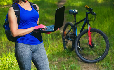 The girl rides a biker after a trip to the pine forest and makes a further route on the laptop.