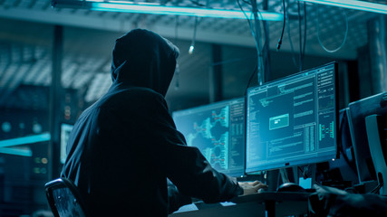 Shot from the Back to Hooded Hacker Breaking into Corporate Data Servers from His Underground Hideout. Place Has Dark Atmosphere, Multiple Displays, Cables Everywhere. Wall mural