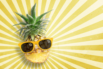 Pineapple wearing sunglasses on sunbeam vintage background with copy space and pastel tone. In summer holiday.