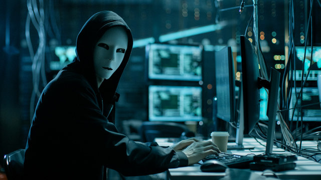 Masked Hacker is Using Computer for Organizing Massive Data Breach Attack on Corporate Servers. They're in Underground Secret Location Surrounded by Displays and Cables.