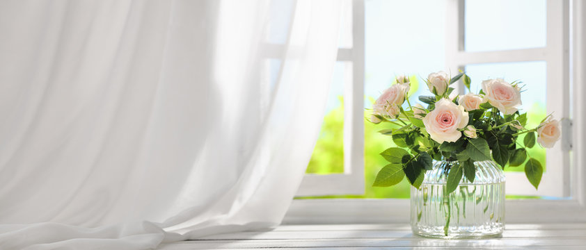 Bouquet of rose flowers near window