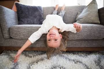 Girl lying upside on a sofa in a living room
