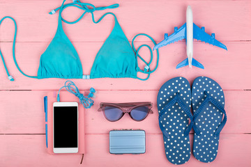 Travel concept - summer women's fashion with blue swimsuit, sunglasses, smart phone, headphones, flip flops, note pad and little airplane and suitcase