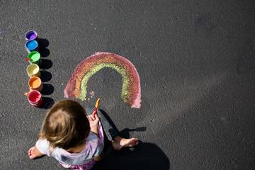 Girl painting rainbow on floor, overhead view