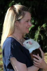 attractive woman holding a genuia pig on her arm