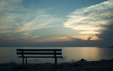 Bench by the sea at sunset