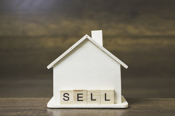 House model with Sell word on wooden blocks.