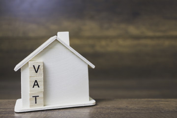 House model with vat word on wooden blocks.