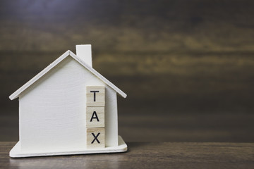 House model with tax word on wooden blocks